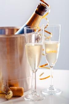 Par de taça de champanhe com garrafa em recipiente de metal