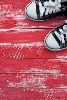 Par de tênis azuis em um canto de um fundo vermelho gasto, composição vertical