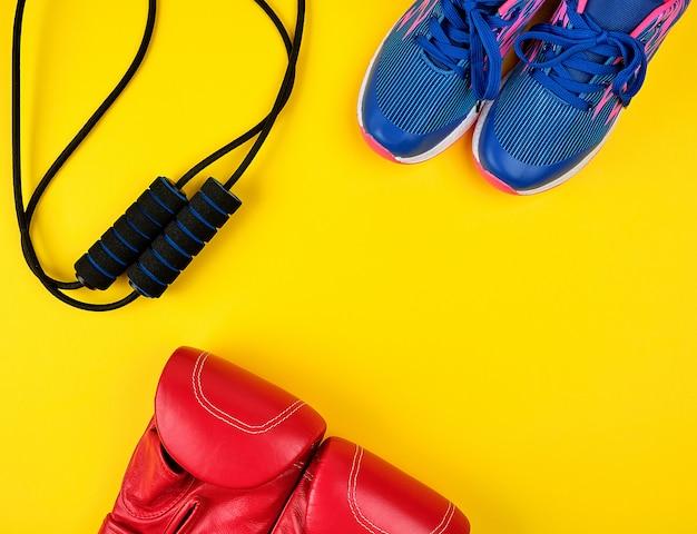 Par de tênis azuis, luvas de boxe de couro vermelho