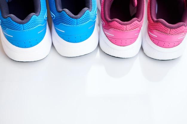 Par de tênis azul masculino e par de tênis rosa feminino em fundo branco.