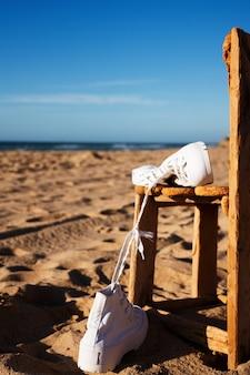 Par de tênis brancos em uma velha cadeira de madeira na praia.