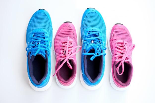 Par de tênis de corrida azuis para homens e par de rosa um para mulheres em fundo branco.