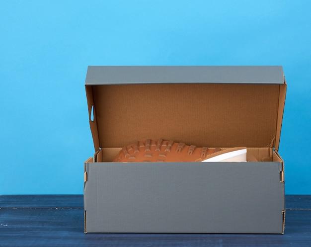 Par de tênis de couro em uma caixa de papelão cinza
