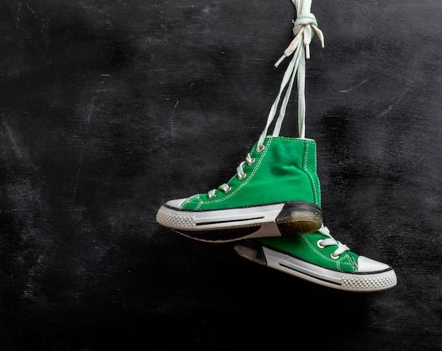 Par de tênis desgastados de têxteis verdes pendurar