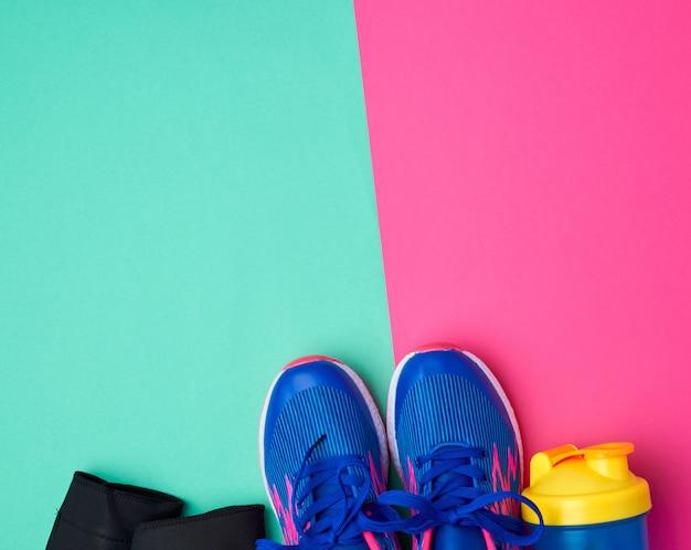 Par de tênis esportivos com atacadores azuis em um fundo abstrato colorido