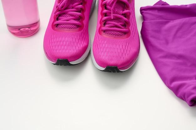 Par de tênis esportivos têxteis roxos em um fundo branco. roupa de esporte