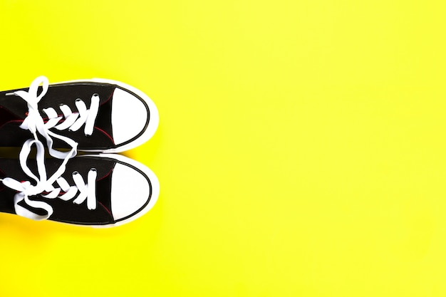 Par de tênis preto e branco sobre fundo amarelo brilhante.