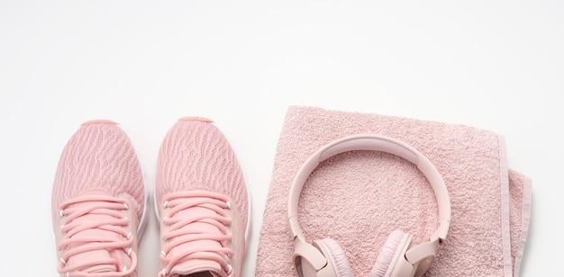 Par de tênis rosa têxtil, fones de ouvido sem fio e uma toalha rosa têxtil em um fundo branco. preparado para esportes, corrida
