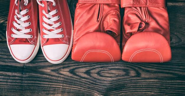 Par de tênis vermelho e luvas de boxe de couro vermelho
