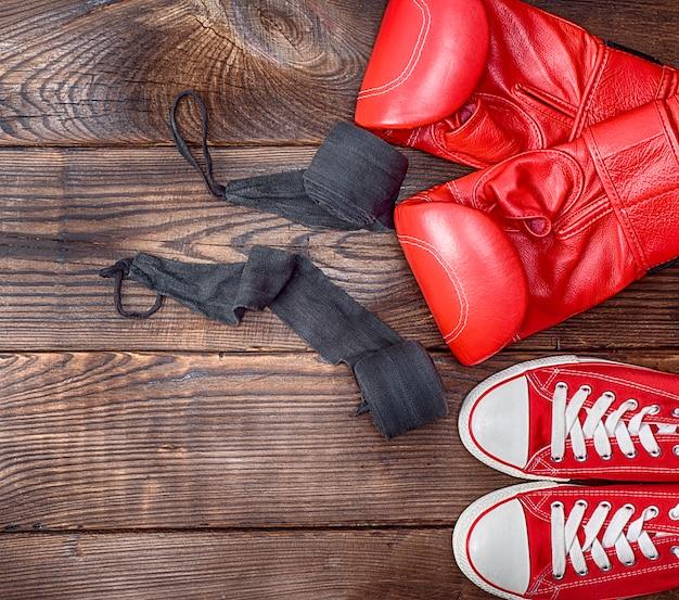 Par de tênis vermelho têxtil e luvas de boxe de couro vermelho