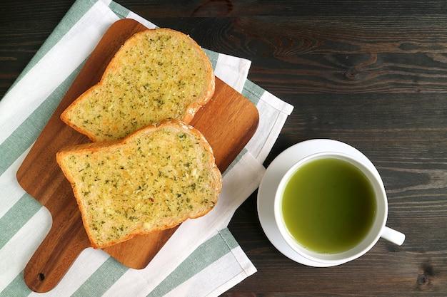Par de torradas de manteiga de alho na tábua de pão com uma xícara de chá verde quente na mesa de madeira
