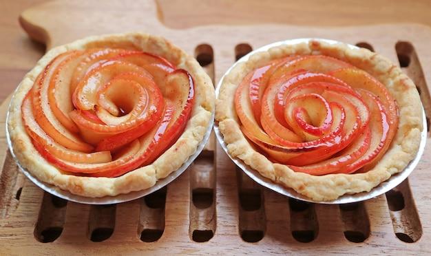 Par de tortinhas de rosa de maçã caseiras frescas assadas na tábua de pão de madeira