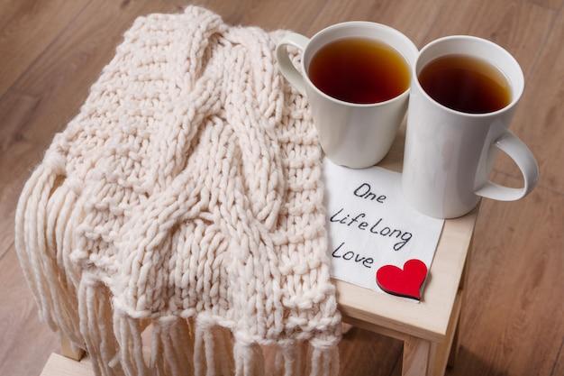 Par de xícaras, cachecol quente, em casa interior