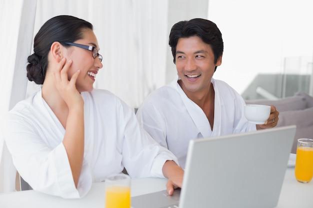 Par, em, bathrobes, gastando, a, manhã, junto, usando computador portátil