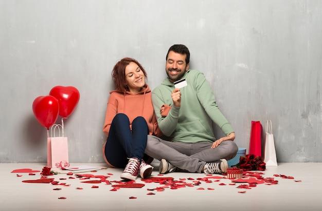 Par, em, dia valentine, segurando, um, cartão crédito, e, pensando