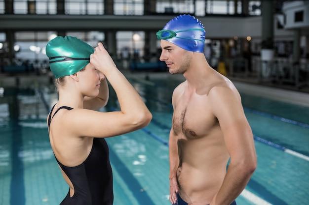 Par, em, swimsuits, olhando um ao outro, em, a, piscina