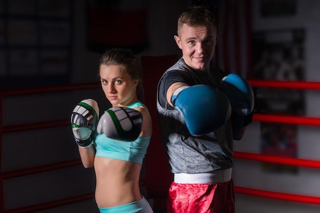 Par esportivo em roupas esportivas e luvas de boxe em pé no ringue de boxe normal em uma academia