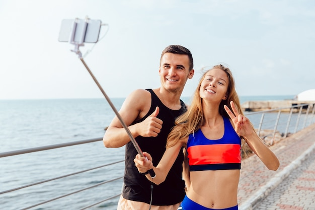 Par feliz, em, sportswear, mostrando, um, polegar cima, e, sinal paz, enquanto, levando, um, selfie