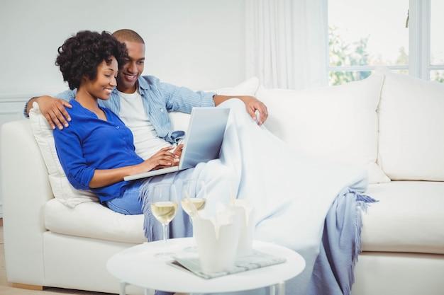Par feliz, ligado, a, sofá, usando computador portátil, com, glasss, de, vinho branco, ligado, tabela