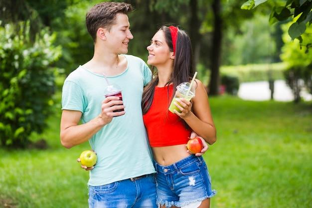 Par, ficar, parque, segurando, saudável, smoothies, e, maçãs, olhando um ao outro