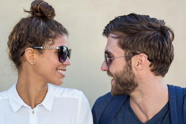 Par hip, com, óculos de sol, olhando um ao outro