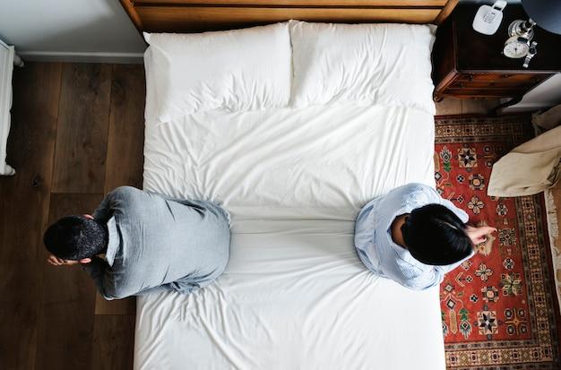 Par interracial, sentando, costas, cama