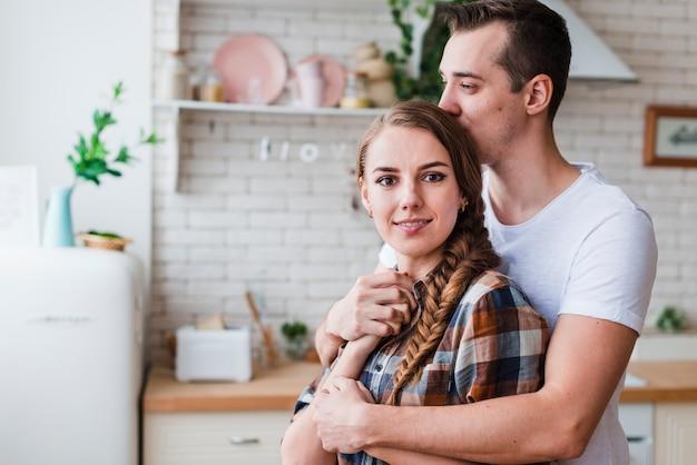Par jovem, abraçando, e, beijando, em, cozinha