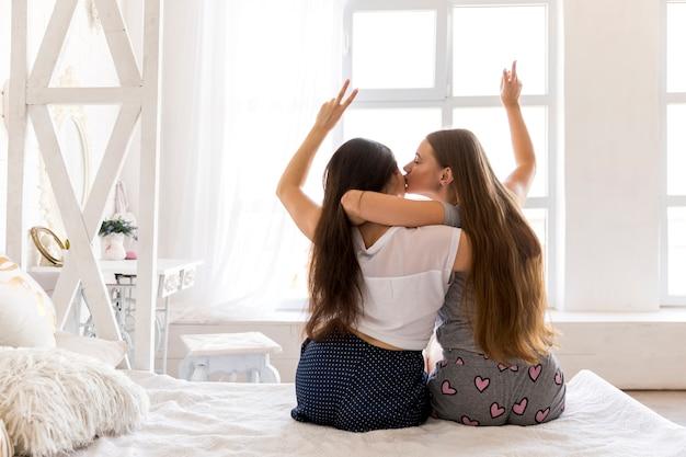 Par jovem, abraçando, e, fazendo, sinal paz