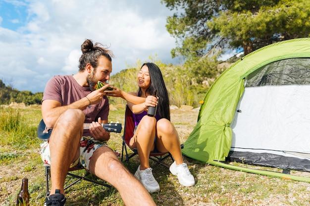 Par jovem, acampamento, gramado