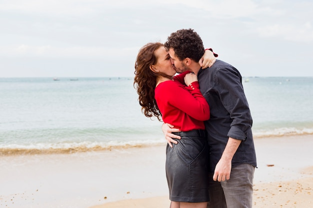 Par jovem, beijando, ligado, costa mar
