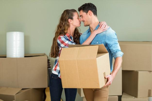 Par jovem, beijando, um ao outro, enquanto, desembalando, caixas cartão, em, casa nova