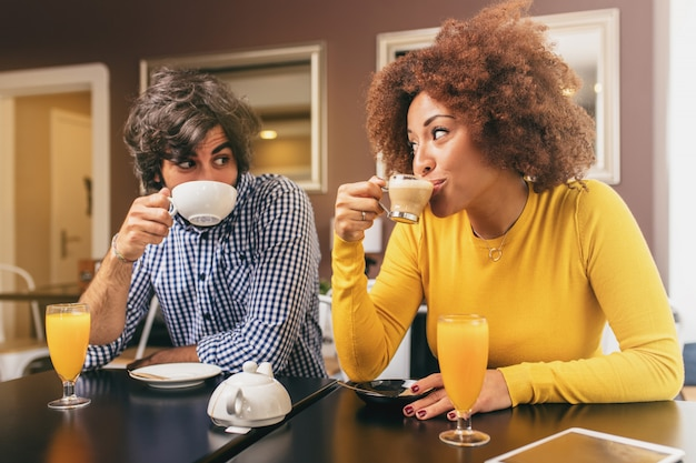 Par jovem, café bebendo, e, um, suco laranja, olhando um ao outro