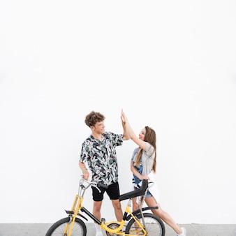 Par jovem, com, bicicleta, ficar, ligado, calçada, dar, alto cinco