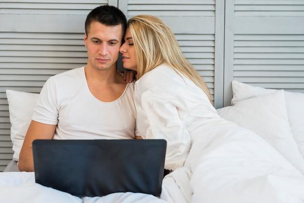 Par jovem, com, laptop, e, cobertor, cama