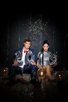 Par jovem, com, prata, balões, números, e, ornamento, bolas