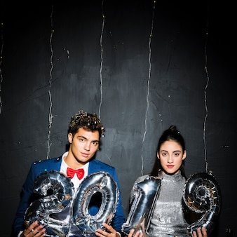 Par jovem, com, prata, balões, números