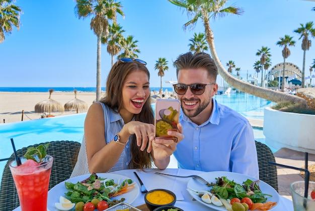 Par jovem, com, smartphone, em, restaurante piscina