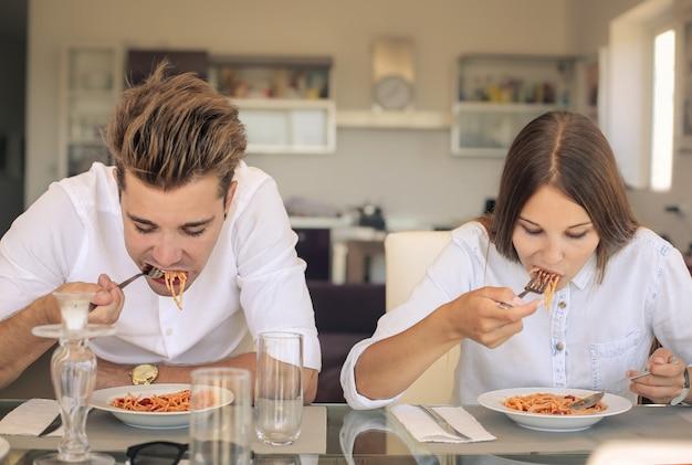 Par jovem, comendo macarrão