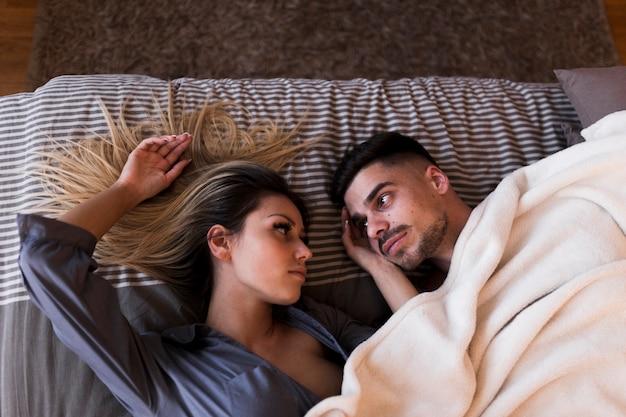 Par jovem, dormir cama, olhando um ao outro