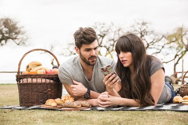 Par jovem, em, piquenique, olhando telefone móvel