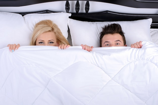 Par jovem, em, um, cama, olhar, de, sob, cobertor