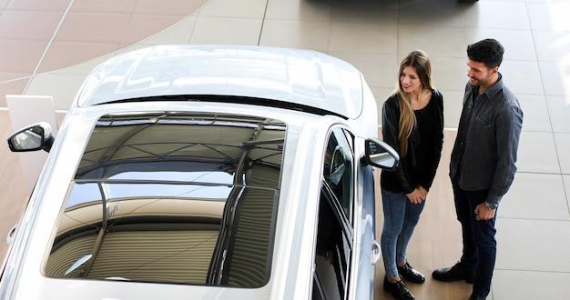 Par jovem, escolher, carro novo, para, comprando, em, concessionária, loja