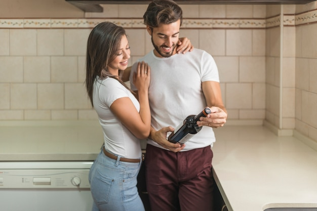 Par jovem, examinando, garrafa vinho