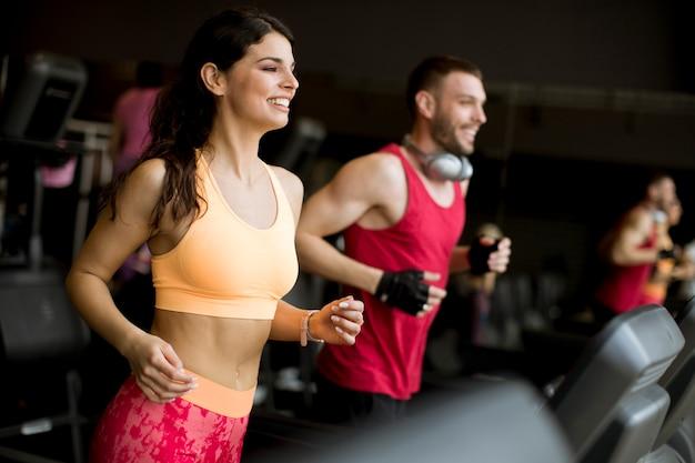 Par jovem, executando, ligado, treadmills, em, modernos, ginásio
