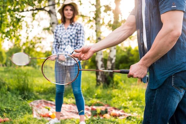 Par jovem, jogando badminton, ligado, piquenique