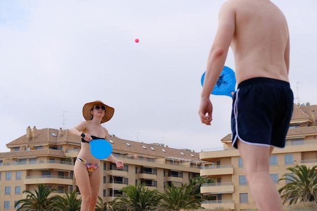 Par jovem, jogando, bola quebra, praia, tênis