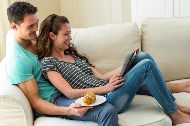 Par jovem, jornal leitura, ligado, sofá, em, sala de estar