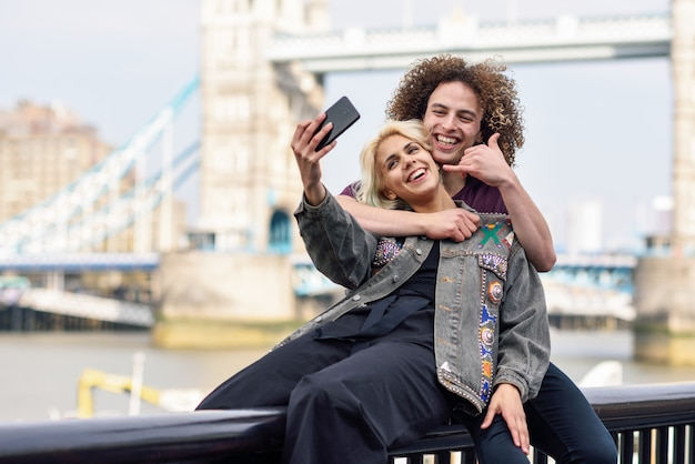 Par jovem, levando, selfie, fotografia, em, a, ponte torre