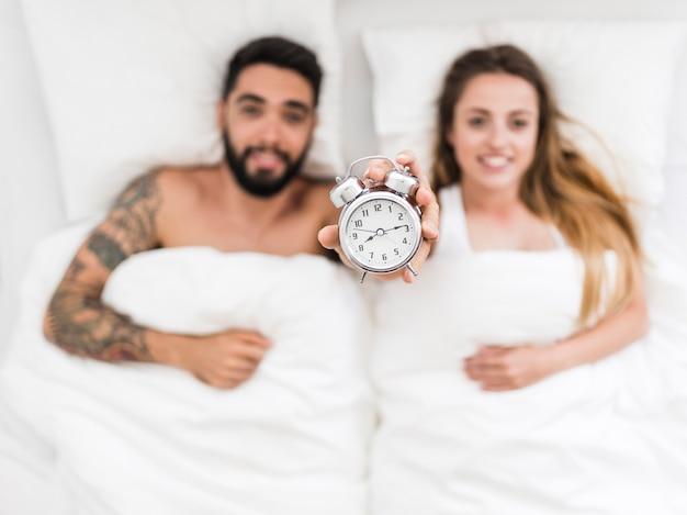 Par jovem, mentindo, cama, mostrando, despertador