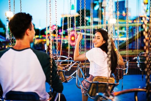 Par jovem, montando, a, balanços, em, um, parque divertimento